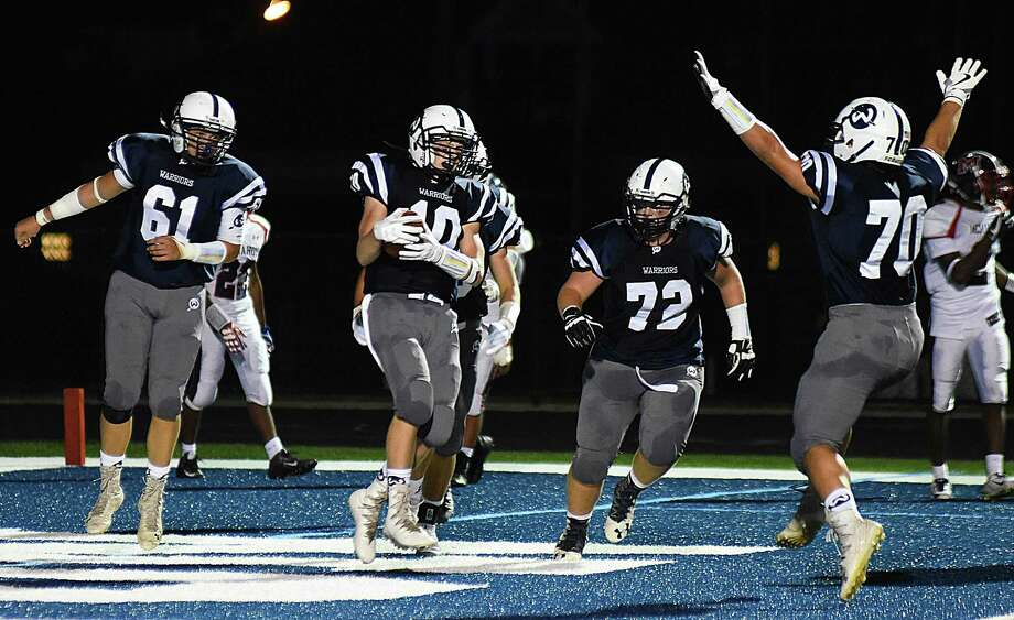 Wilton's Kyle Phillips (10) scores his second of three touchdowns and celebrates with teammates during the Warriors' 42-21 win over Brien McMahon on Friday at Fujitani Field in Wilton. Photo: John Nash / Hearst Connecticut Media / Norwalk Hour