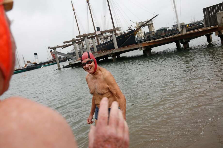 Above: Bob McKenzie, a member of the Dolphin Club, prepares to swim in the cold water of Aquatic Park. Left: John Robiola returns a boat to the Dolphin Club. Photo: Lea Suzuki, The Chronicle