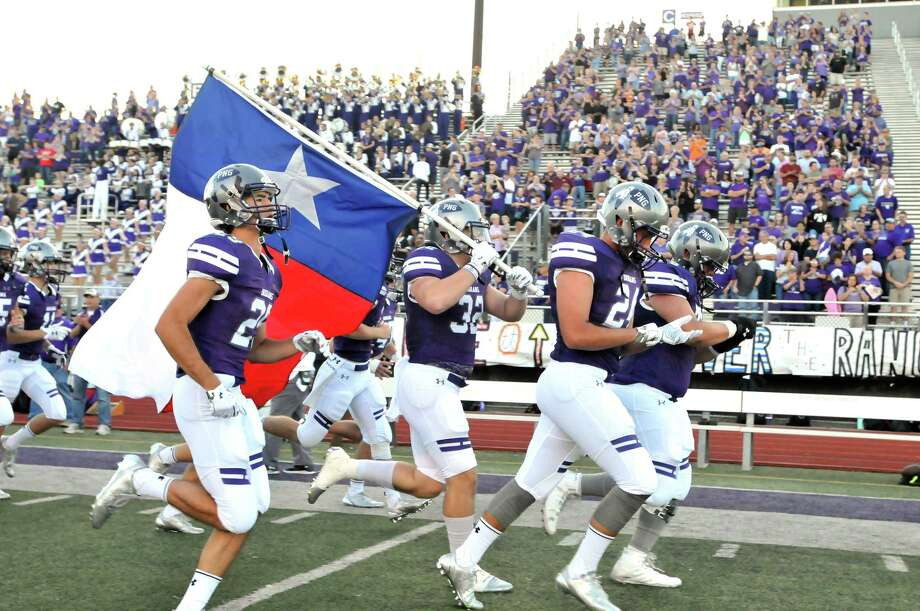 Port Neches-Groves' Andrew Hebert carries a Texas flag onto the field as the Indians football team sprints toward the opposite end zone before Friday game against Baytown Sterling at Indian Stadium. (Mike Tobias/The Enterprise) Photo: Mike Tobias/The Enterprise