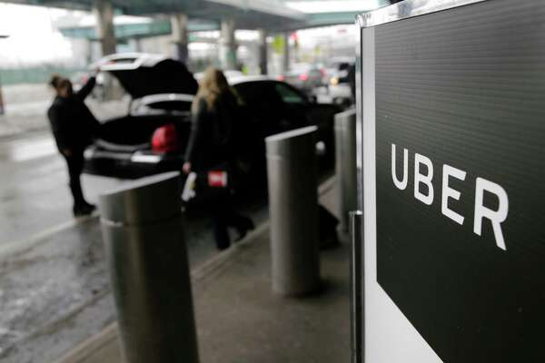 FILE - In this March 15, 2017, file photo, a sign marks a pick up point for the Uber car service at LaGuardia Airport in New York. The Justice Department in Manhattan is investigating whether Uber illegally used software to track drivers for Lyft, its main ride-hailing competitor, to gain an advantage in attracting and recruiting drivers, according to two people familiar with the probe. The FBI and the U.S. Attorney's Office in New York's Southern District want to know if use of the software, which created fake customer accounts, broke any federal laws, said the people, who didn't want to be identified because they were not authorized to discuss the case publicly. An Uber spokeswoman said Friday, Sept. 8 it is cooperating in the probe and that use of the software has been discontinued. The U.S. Attorney's Office would not comment on the case. (AP Photo/Seth Wenig, File)