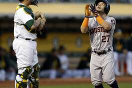 Houston Astros' Jose Altuve, right, celebrates in front Oakland Athletics catcher Bruce Maxwell after hitting a two-run home run off A's Jharel Cotton in the first inning of a baseball game Friday, Sept. 8, 2017, in Oakland, Calif. (AP Photo/Ben Margot)