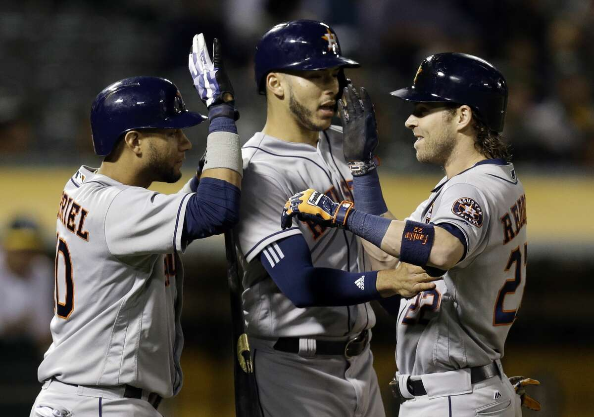 Houston Astros' Josh Reddick, right, celebrates with Yuli Gurriel (10) and Carlos Correa after hitting a two-run home run off Oakland Athletics' Jharel Cotton during the fifth inning of a baseball game Friday, Sept. 8, 2017, in Oakland, Calif. (AP Photo/Ben Margot)