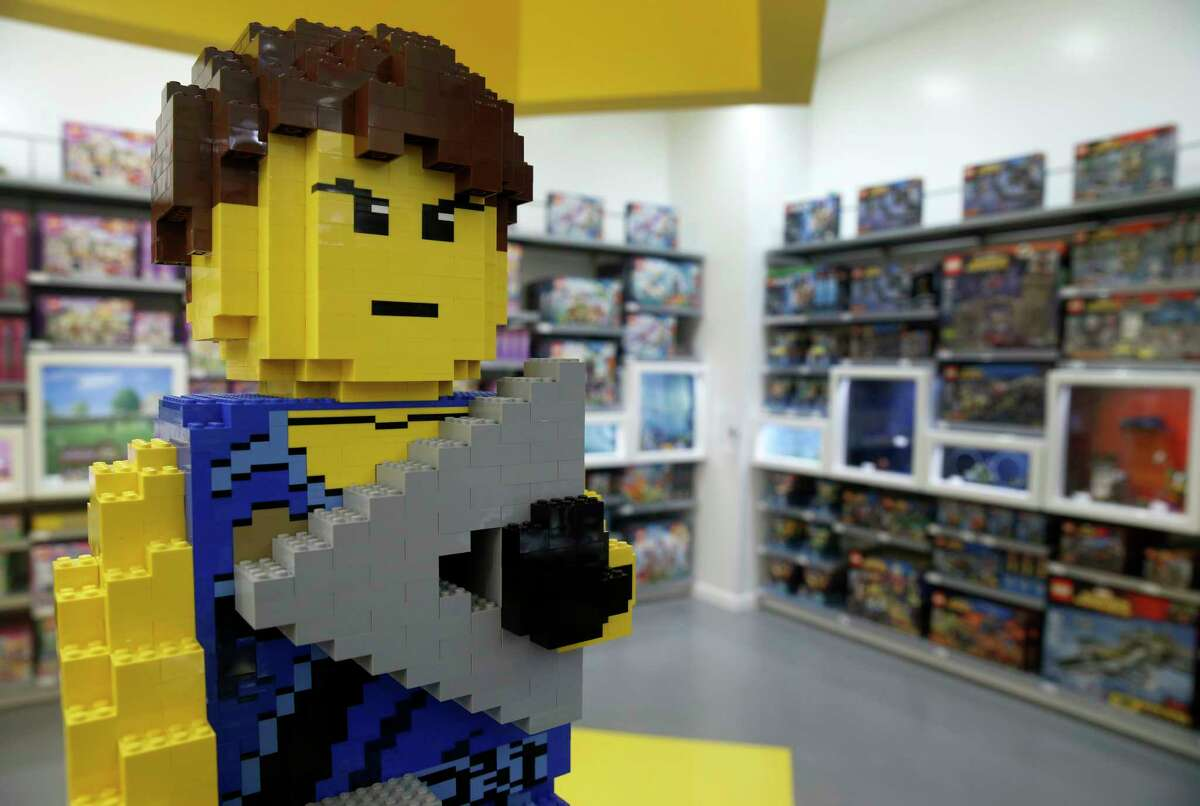 A model of Jay, from Lego Ninjago, stands guard at a Lego store opening in San Francisco. Lego is cutting 8 percent of its workforce.