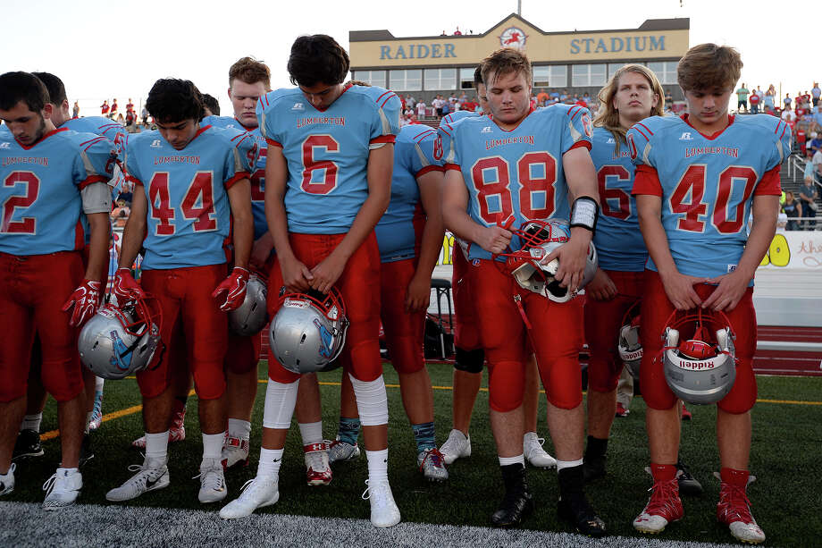 Lumberton players bow their heads for a moment of silence for flooding victims before playing Hamshire-Fannett at Raider Stadium on Friday night. The game marked the return of football after flooding from Hurricane Harvey devastated the region.  Photo taken Friday 9/8/17 Ryan Pelham/The Enterprise Photo: Ryan Pelham / ©2017 The Beaumont Enterprise/Ryan Pelham