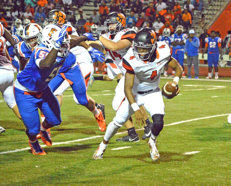 Edwardsville quarterback Kendall Abdur-Rahman, right, tries to elude East St. Louis defender Terrion Williams during the third quarter of Friday's game at East St. Louis.