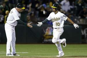 Oakland Athletics' Marcus Semien, right, is congratulated by third base coach Steve Scarsone after hitting a grand slam off Houston Astros' Luke Gregerson during the seventh inning of a baseball game Friday, Sept. 8, 2017, in Oakland, Calif. (AP Photo/Ben Margot)6