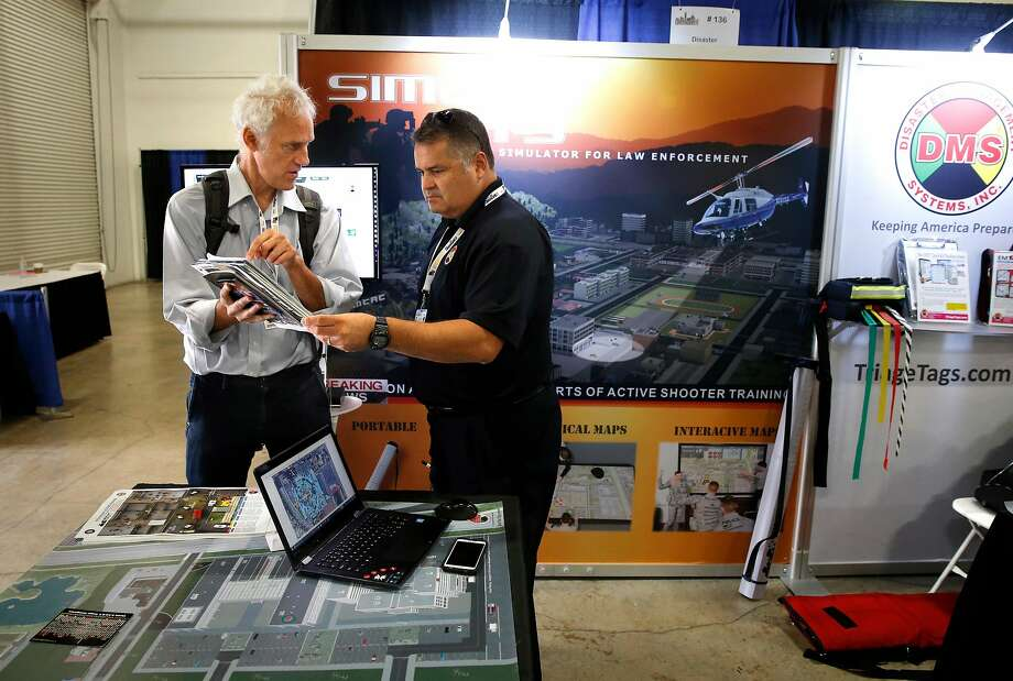 John Lindsay-Poland (left) of the Urban Shield Task Force visits with David Crowl of Disaster Management Systems. Photo: Michael Macor, The Chronicle