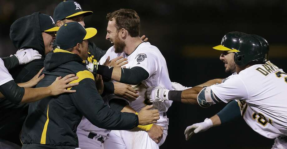 Oakland Athletics' Jed Lowrie, center, is mobbed by teammates after making the game winning hit against the Houston Astros in the ninth inning of a baseball game Friday, Sept. 8, 2017, in Oakland, Calif. (AP Photo/Ben Margot) Photo: Ben Margot/Associated Press
