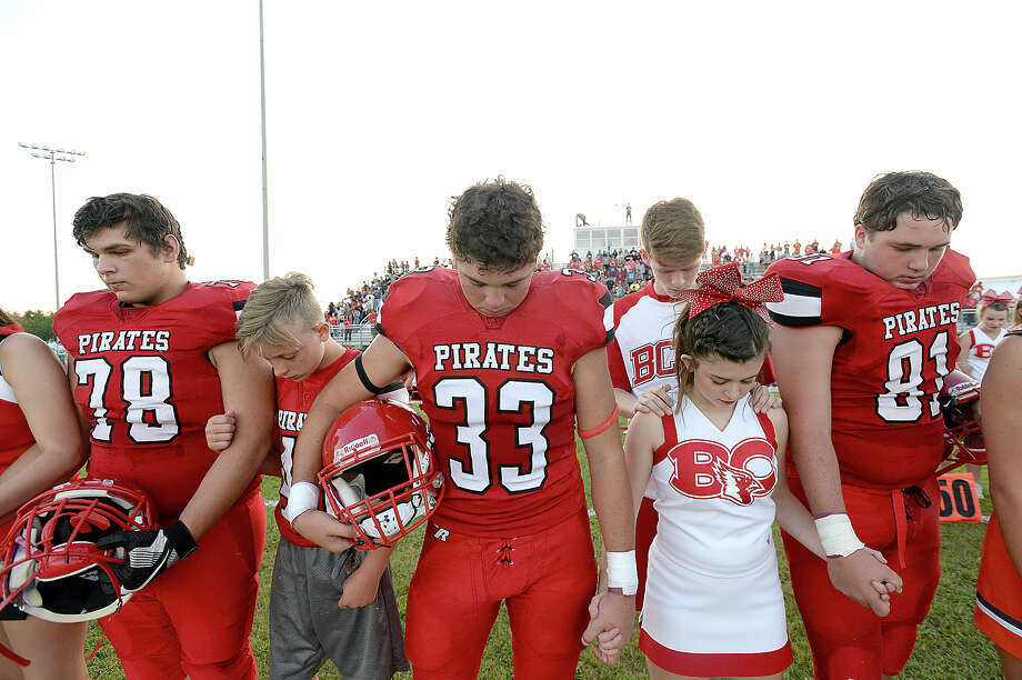 Deweyville's varsity players clasp hands with cheerleaders, which included squads from Bridge City and Orangefield, in a series of pastor prayers at the start of Friday night's football game against Burkeville. Photo taken Friday, September 8, 2017 Kim Brent/The Enterprise Photo: Kim Brent / BEN