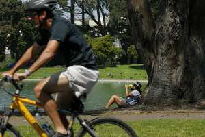 Lisa Hauptman of Santa Rosa hydrates and takes cover from the sun under a tree at Golden Gate Park on Friday, Sept. 1, 2017, in San Francisco, Calif. The National Weather Service issued an excessive heat warning as the San Francisco Bay Area reached temperatures in the upper 90s and some areas surpassed 100 degrees.