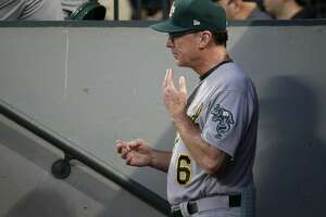 Oakland Athletics Bob Melvin signals a baserunner from the dugout during in the second inning of a baseball game against the Seattle Mariners, Friday, Sept. 1, 2017, in Seattle. (AP Photo/Ted S. Warren)