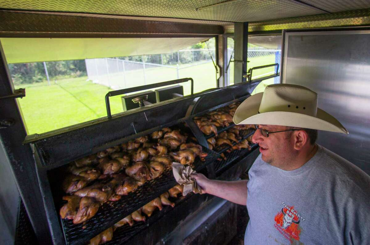 Chaim Goldfeder checks on the chickens smoking in his kosher food trailer, Texas Kosher BBQ, which is serving community members and volunteers outside the Beren Academy in the Willowbend area.
