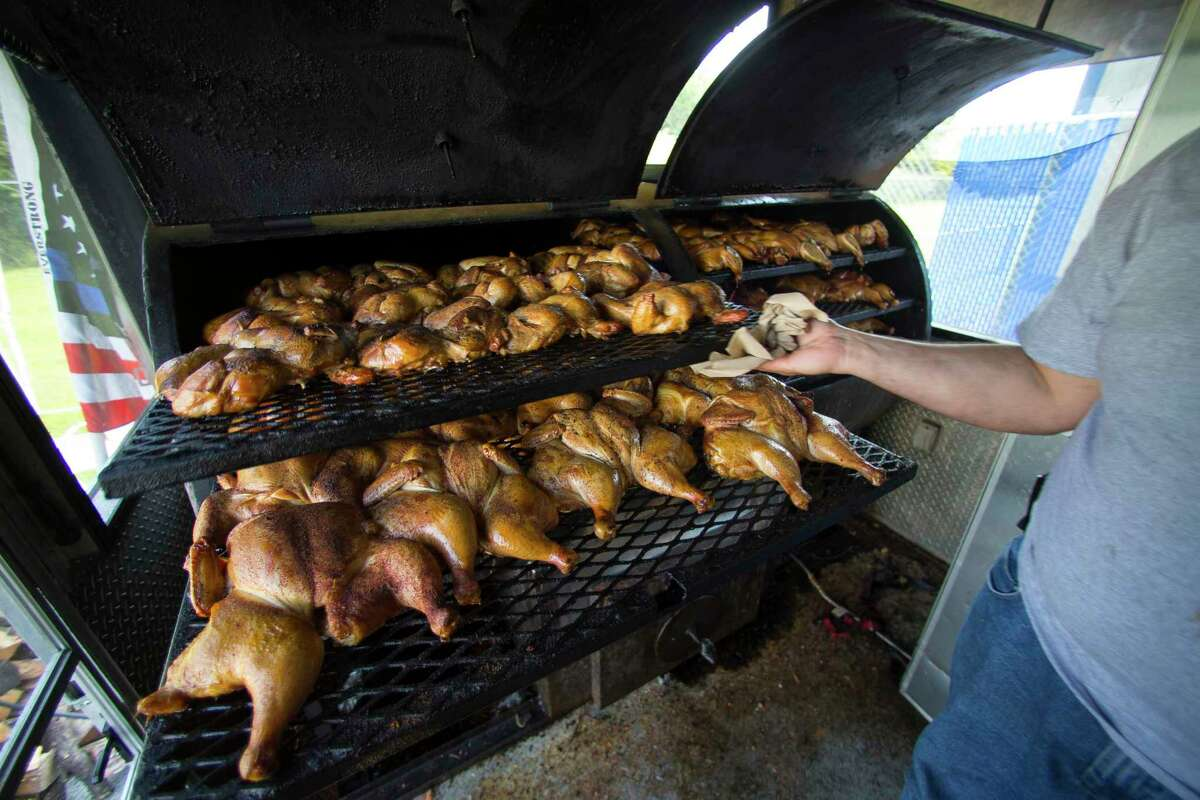 Chaim Goldfeder checks on the chickens smoking in his kosher food trailer, Texas Kosher BBQ, that is currently serving community members and volunteers outside of the Beren Academy in the Willowbend area of Houston, Wednesday, September 6, 2017. (Mark Mulligan / Houston Chronicle)