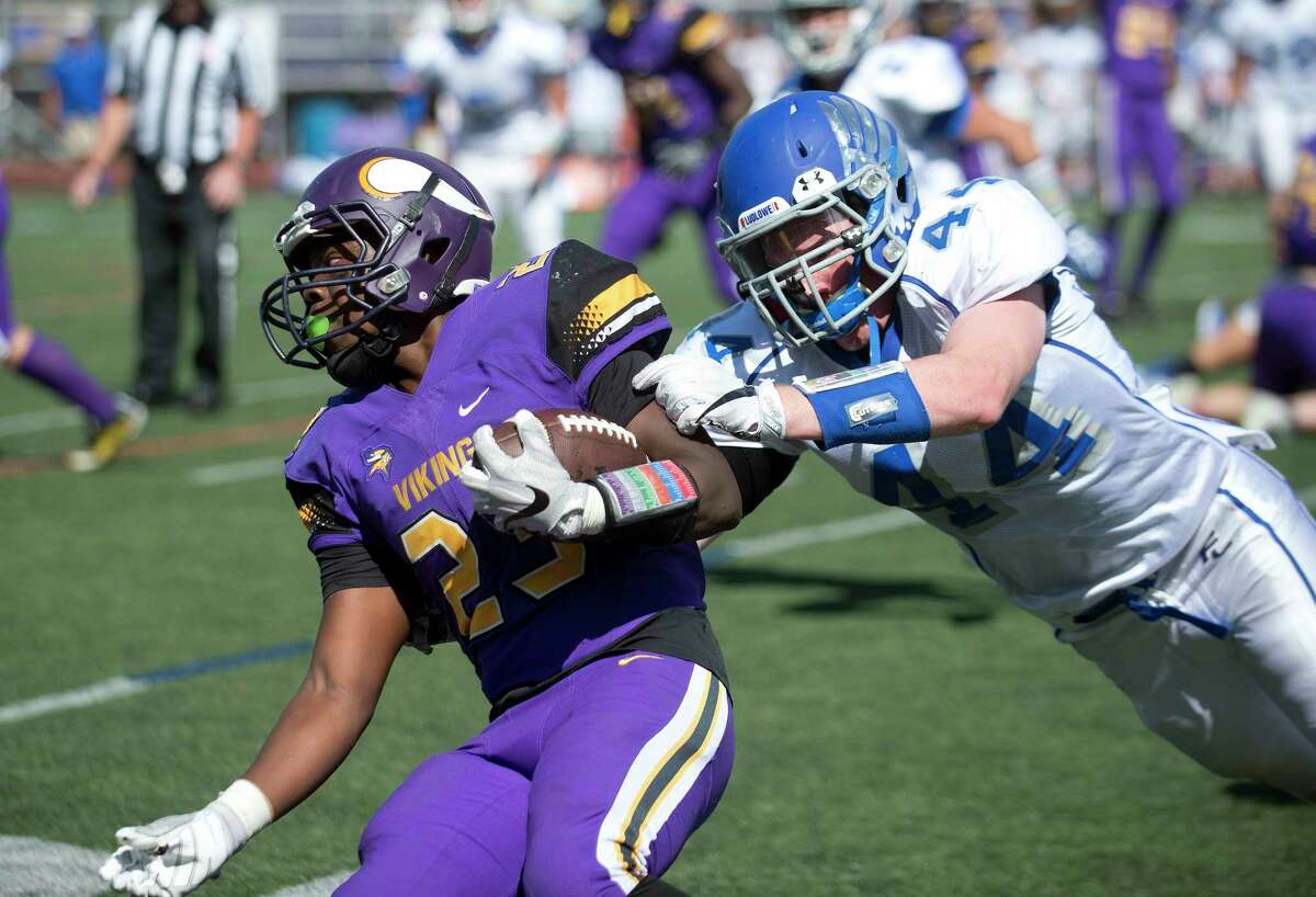 Westhill's Saquan Kelly carries the ball as he is tackled by Fairfield Ludlowe's Jake Northrop during Saturday's football game at Westhill High School in Stamford, Conn., on September 9, 2017.