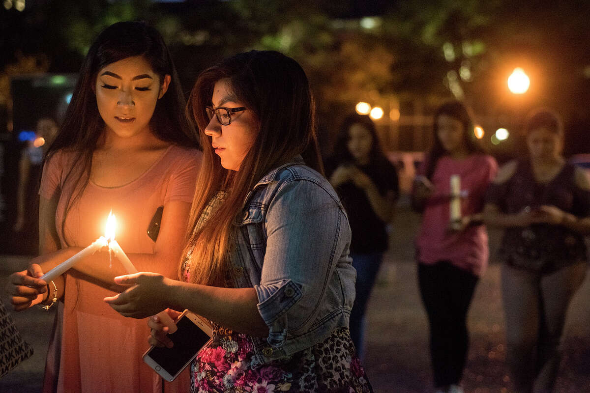 FILE - In this Sept. 5, 2017 file photo, Josselyn and Blanca Villanueva hold candles during a silent vigil in honor of Deferred Action for Childhood Arrivals (DACA) at T.B. Butler Fountain Plaza in Tyler, Texas. Young immigrants in Houston and Miami are scrambling to complete their renewal applications for a program shielding them from deportation while dealing with hurricanes that have hit or are bearing down on their states. An Oct. 5 deadline was announced this week by the Trump administration. It set off an immediate scramble among many of the nearly 800,000 people protected by the DACA program, most notably in Texas and Florida. (Chelsea Purgahn /Tyler Morning Telegraph via AP, File)