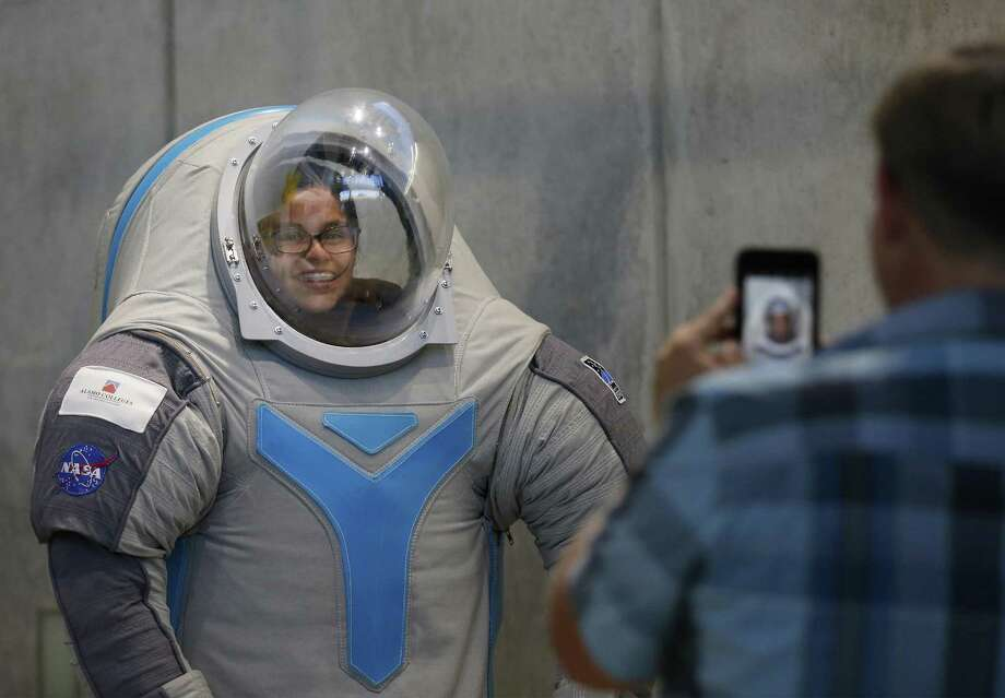 Katelyn Duran, 12, from Judson STEM Academy get her picture taken in a space suit display on Saturday, Sept. 9, 2017. Thirty area middle and high school students attended the first Lunar Caves Analog Test Sites (LCATS) program at Scobee Education Center. The first day included an introduction to the program and then students were set off on their first day of program where they worked on various scientific exercises in the Challenger Learning Center. Photo: Kin Man Hui /San Antonio Express-News / ©2017 San Antonio Express-News