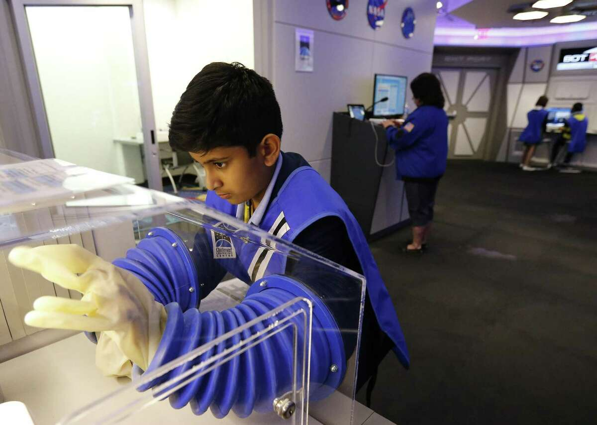 Student Ansh Jakatimath works in a glove booth during a geological experiment at the Challenger Learning Center in the Scobee Education Center on the campus of San Antonio College. The program fosters space-STEM education projects for interested students.