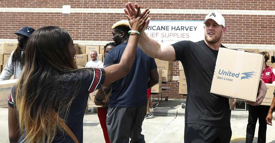 Anna Ucheomumu, left, high fives Houston Texans defensive end J.J. Watt after loading a car with relief supplies to people impacted by Hurricane Harvey on Sunday, Sept. 3, 2017, in Houston. Watt's Hurricane Harvey Relief Fund has raised millions of dollars to help those affected by the storm. (Brett Coomer/Houston Chronicle via AP, Pool) Photo: Brett Coomer/Associated Press