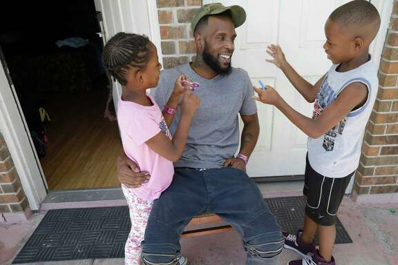 Natalie Spears, 8, and her brother Christopher Spears, 9, show  Brandon Polson their fidget spinners while in the Humble area motel Thursday, Sept. 7, 2017, where the family is staying after escaping their flooded apartment in the aftermath of Hurricane Harvey. The family has a hotel voucher from FEMA for temporary lodging through Sept. 25 and they're not sure where they'll go next. They recieved donated shoe while in a shelter.