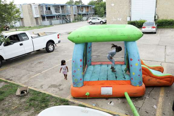 ***to go with Rebecca's story****Monica Cruz, 7, jumps in an inflatable bouncy house as her neighbor Ashley Guerrero Monterrosa, 2, walks in the parking lot as residents clean up from Tropical Storm Harvey at Rockport Apartments on Tuesday, Sept. 5, 2017, in Houston. The apartments were hit with a tornado in 2015.