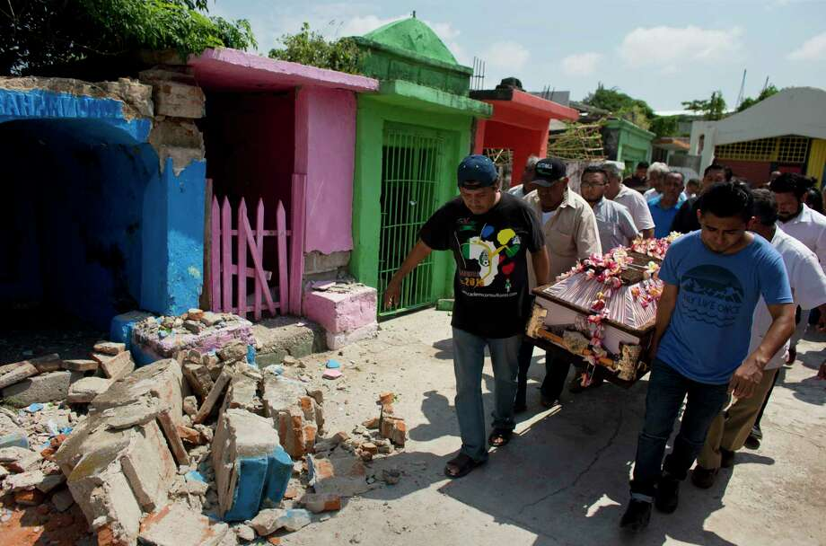 Men carry the coffin of 64-year-old Reynalda Matus past earthquake debris in Juchitan, Mexico, on Saturday. Matus was killed when the pharmacy she worked at collapsed during Thursday's massive 8.1 earthquake.  Photo: Rebecca Blackwell, STF / Copyright 2017 The Associated Press. All rights reserved.