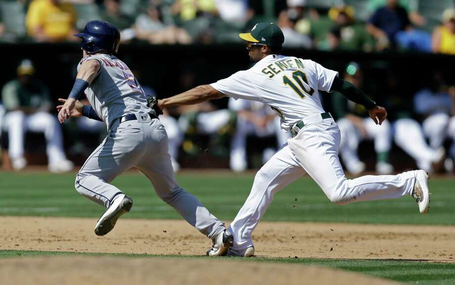 Houston Astros' Alex Bregman, left, is tagged out in a rundown between second and third base by Oakland Athletics' Marcus Semien (10) in the fifth inning of the first baseball game of a doubleheader on Saturday, Sept. 9, 2017, in Oakland, Calif. (AP Photo/Ben Margot) Photo: Ben Margot, STF / Copyright 2017 The Associated Press. All rights reserved.