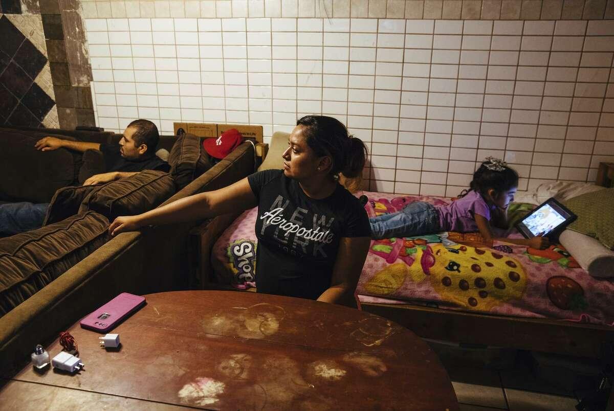Erika Almanza (center) watches the news as daughter Jocelyn Cuevas, 7, views a program on her iPad.