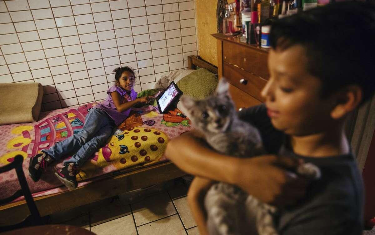 Erika Almanza children, Jocelyn Cuevas, 7 and Angel Almanza, 11, hang out in their apartment in San Jose.