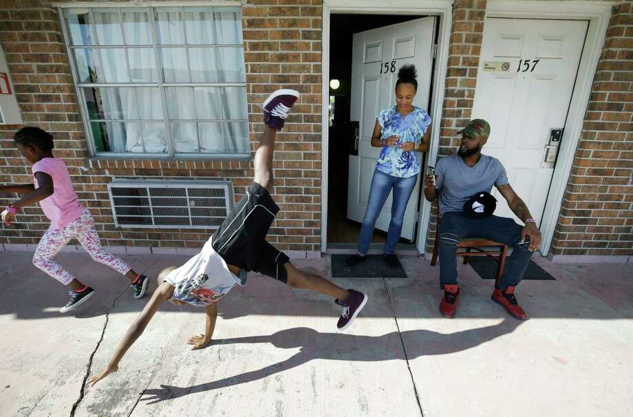 Natalie Spears, 8, and her brother, Christopher Spears, 9, play as their mother, Dé•Ona Spears, watches and  Brandon Polson takes a video outside the Humble area motel Thursday, Sept. 7, 2017, where the family is staying after escaping their flooded apartment in the aftermath of Hurricane Harvey. The family has a hotel voucher from FEMA for temporary lodging through Sept. 25 and they're not sure where they'll go next.  ( Melissa Phillip / Houston Chronicle ) Photo: Melissa Phillip, Staff / © 2017 Houston Chronicle