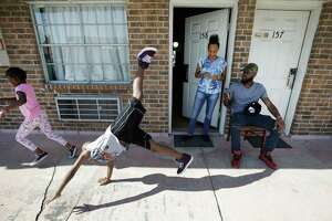 Natalie Spears, 8, and her brother, Christopher Spears, 9, play as their mother, D'Ona Spears, watches and  Brandon Polson takes a video outside the Humble area motel Thursday, Sept. 7, 2017, where the family is staying after escaping their flooded apartment in the aftermath of Hurricane Harvey. The family has a hotel voucher from FEMA for temporary lodging through Sept. 25 and they're not sure where they'll go next.  ( Melissa Phillip / Houston Chronicle )