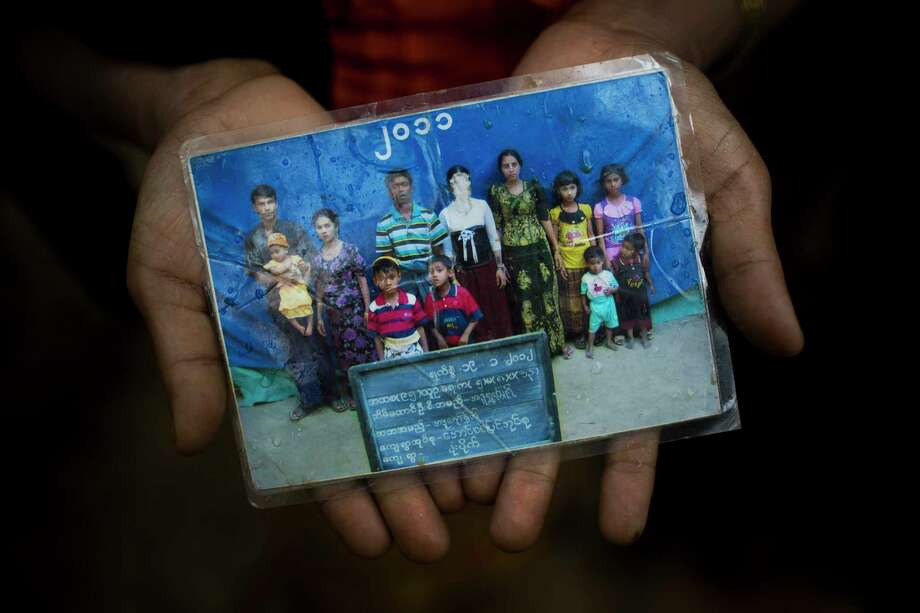 In this Sept. 8, 2017, photo, Rohingya Mubarak Begum, who crossed over from Myanmar into Bangladesh, holds a photograph of her family members, in Kutupalong, Bangladesh, Begum says the government took pictures of Rohingya families annually to track their numbers. Her daughter Rubina Begum (face scratched ) was not able to make the crossing with them and still in Maungdaw. Don't expect the United States to step in and resolve what is increasingly being describing as an ethnic cleansing campaign against Myanmar's downtrodden Rohingya Muslims.(AP Photo/Bernat Armangue) Photo: Bernat Armangue, STF / Copyright 2017 The Associated Press. All rights reserved.