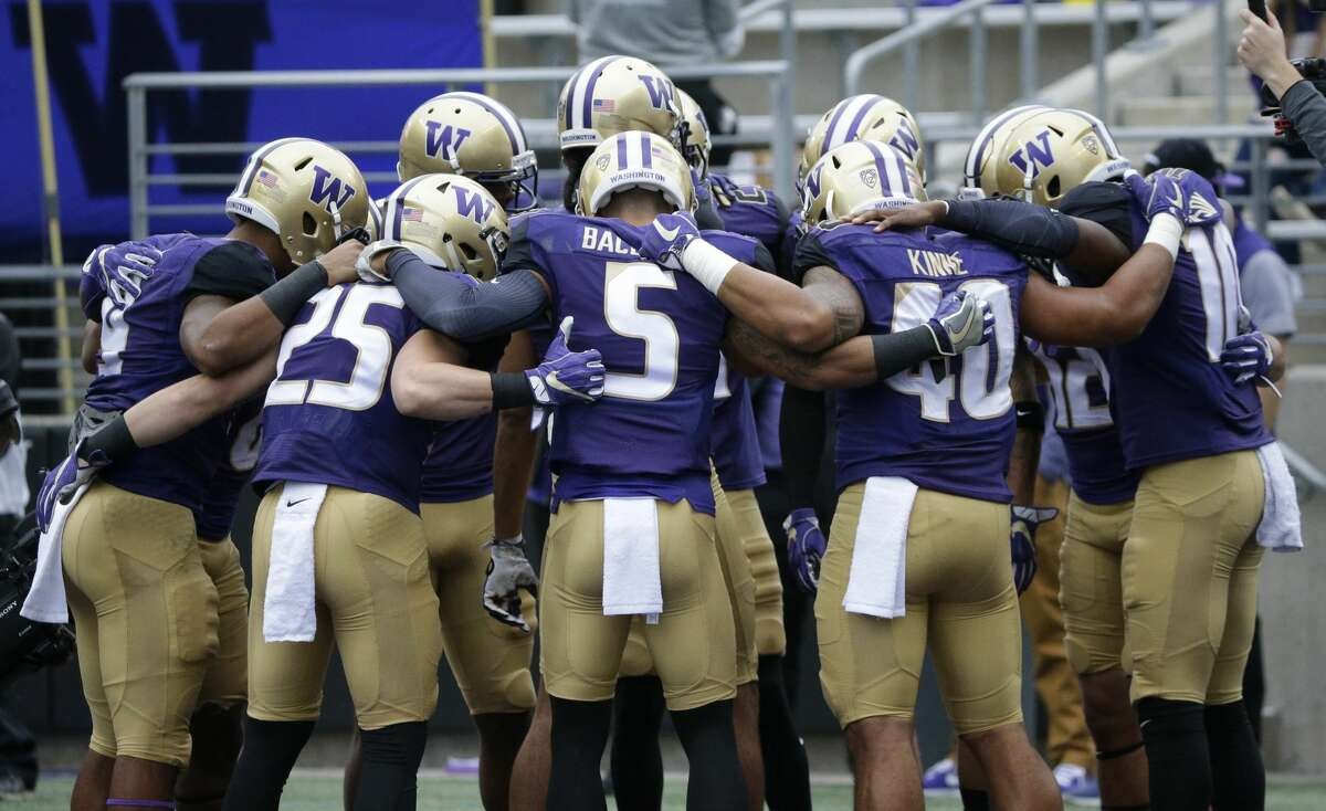 Washington players huddle during warmups before an NCAA college football game against Montana, Saturday, Sept. 9, 2017, in Seattle. (AP Photo/Ted S. Warren)