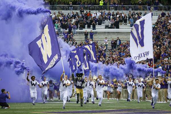 Washington cheerleaders and Harry, the Husky mascot, set off smoke effects as they lead the team out of the tunnel at Husky Stadium for Washington's home opener, an NCAA college football game against Montana, Saturday, Sept. 9, 2017, in Seattle. (AP Photo/Ted S. Warren)