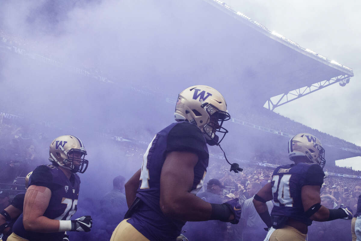 The University of Washington runs onto the field for their first home game, against Montana on Saturday, Sept. 9, 2017.