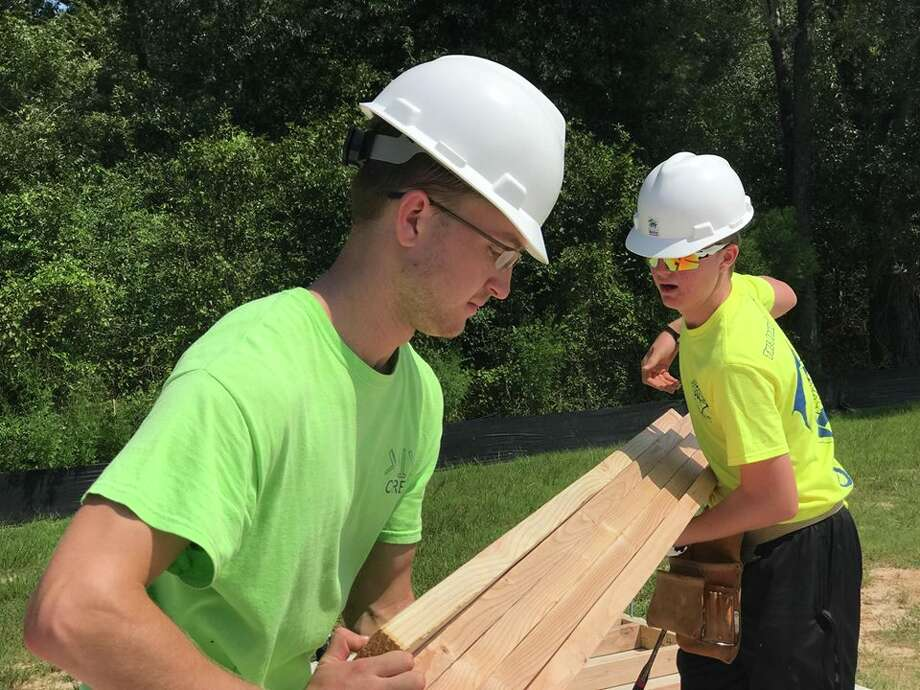 Spring resident and recent Texas A&M graduate John Cuyler Burton, 23, held a plank steady as his younger brother Callum Burton, 16, hammered on the foundation of a new home for a Conroe family. Photo: Meagan Ellsworth
