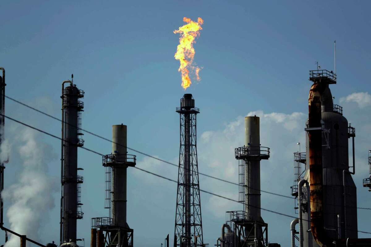 FILE - In this Thursday, Aug. 31, 2017, file photo, a flame burns at the Shell Deer Park oil refinery in Deer Park, Texas. Companies have reported that roughly two dozen storage tanks holding crude oil, gasoline and other fuels collapsed or otherwise failed during Harvey, spilling a combined 140,000 gallons of fuel, according to an Associated Press analysis of state and federal accident databases. Federal rules require companies to be prepared for spills, but don't require them to take any specific measures to secure the massive fuel storage tanks at refineries and oil production sites that are prone to float and break during floods. (AP Photo/Gregory Bull, File)