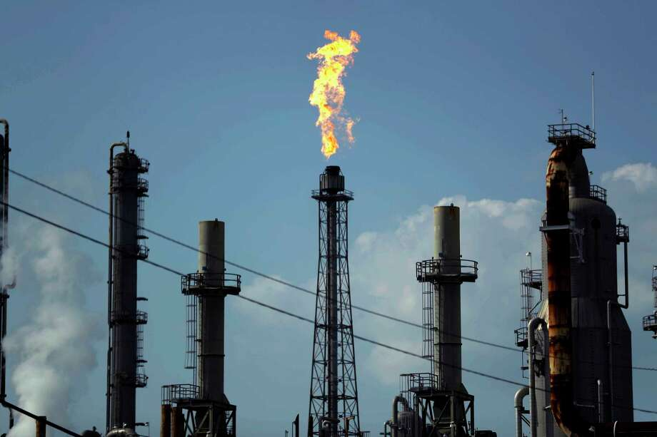 FILE - In this Thursday, Aug. 31, 2017, file photo, a flame burns at the Shell Deer Park oil refinery in Deer Park, Texas. Companies have reported that roughly two dozen storage tanks holding crude oil, gasoline and other fuels collapsed or otherwise failed during Harvey, spilling a combined 140,000 gallons of fuel, according to an Associated Press analysis of state and federal accident databases. Federal rules require companies to be prepared for spills, but don't require them to take any specific measures to secure the massive fuel storage tanks at refineries and oil production sites that are prone to float and break during floods. (AP Photo/Gregory Bull, File) Photo: Gregory Bull, STF / Copyright 2017 The Associated Press. All rights reserved.
