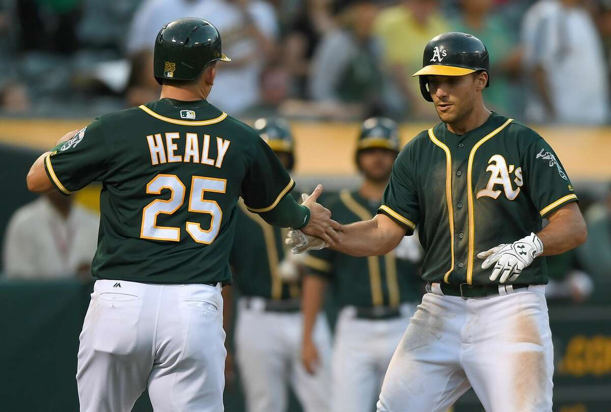 OAKLAND, CA - SEPTEMBER 09: Matt Olson #28 and Ryon Healy #25 of the Oakland Athletics celebrates after Olson hit a two-run homer against the Houston Astros in the bottom of the six inning of the second game in a double header at Oakland Alameda Coliseum on September 9, 2017 in Oakland, California. (Photo by Thearon W. Henderson/Getty Images)