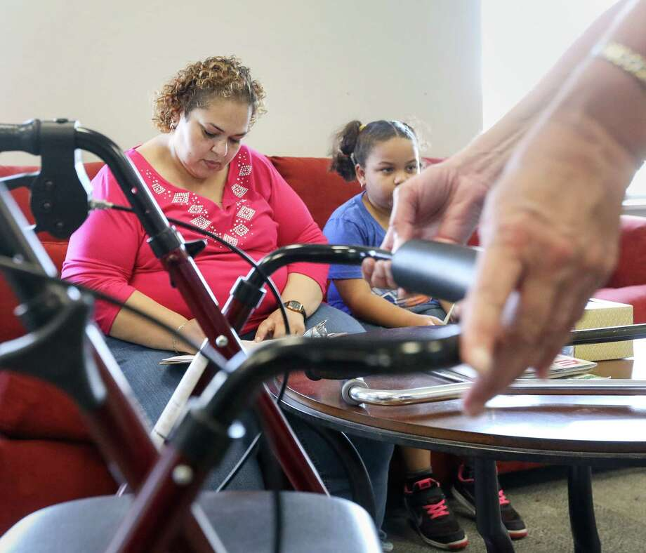 "Patricia Morgan, left, and her daughter Danika, 7, fill out paperwork as Theresa Gregorio-Torres, an occupational therapist, explains the features of Morgan's new walker, during a medical supply donation event, Saturday, Sept. 9, 2017, in Houston. ""I wasn't expecting all of this,"" Morgan said. Photo: Jon Shapley, Houston Chronicle / © 2017 Houston Chronicle"