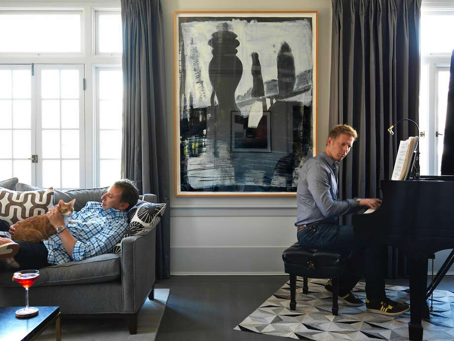 Daniel Maimin snuggles with Oscar the cat while husband Mark Savery plays the Steinway in the living room of their prewar apartment in Lower Nob Hill. The painting is by an unknown artist. Photo: John Lee, Special To The Chronicle