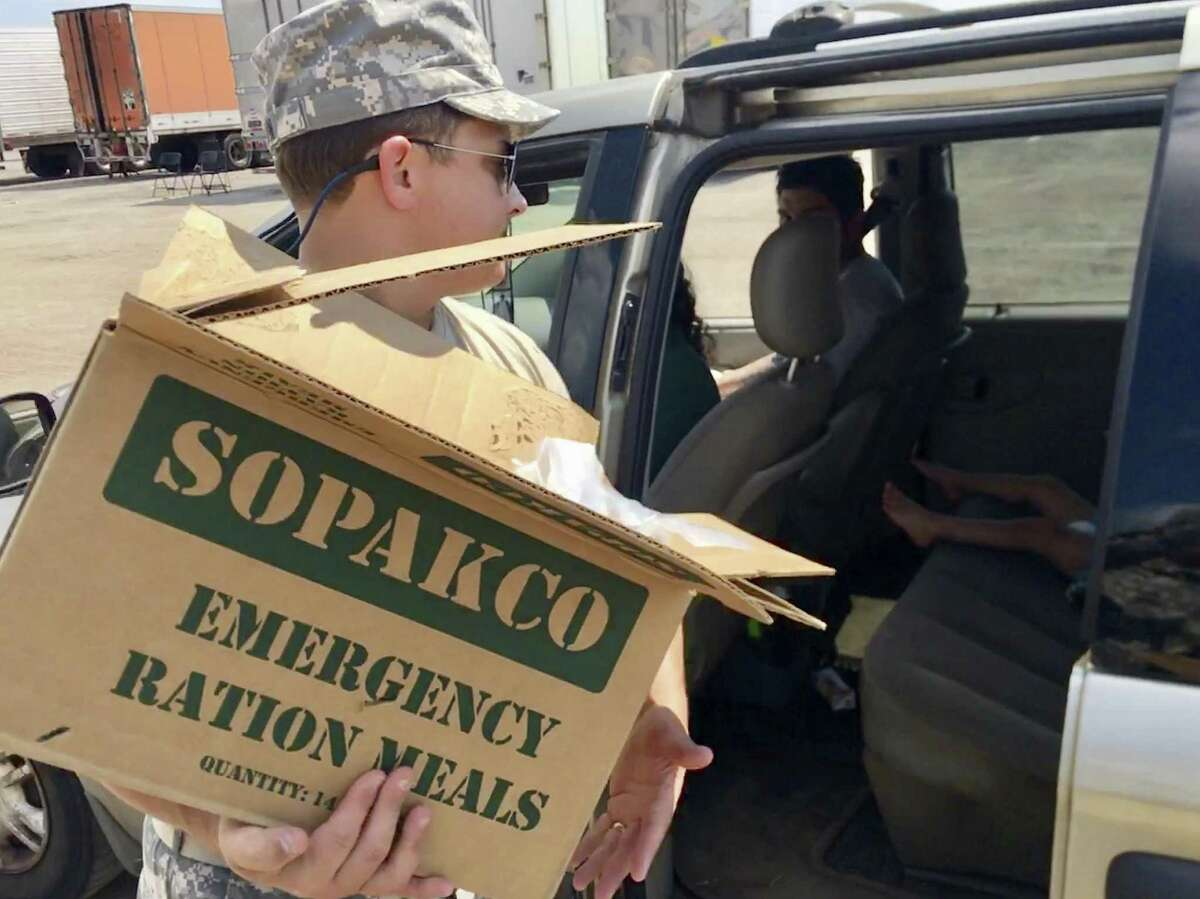 1st Lt. Briscoe Cain, an officer in the Texas State Guard who also is a Republican state representative from Deer Park, loads supplies at a food and water distribution center for people affected by Harvey in Victoria last week.