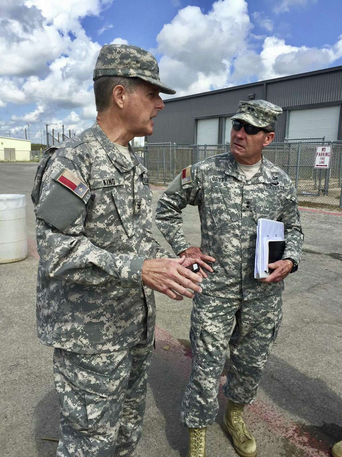 Col. Phil King (left), a Republican state representative from Weatherford, talks with Maj. Gen. Jake Betty on Wednesday at a food and water distribution center in Victoria. The Texas State Guard was called out to help in recovery efforts after Harvey laid waste to much of Southeast Texas.