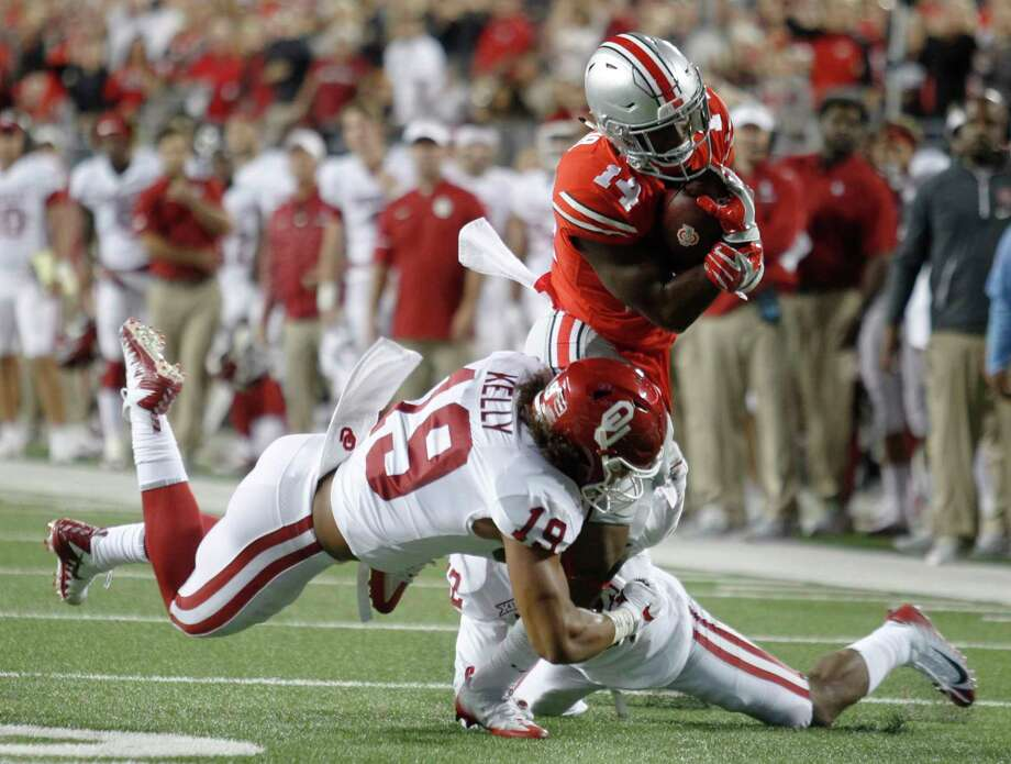 Ohio State receiver K.J. Hill, top, is tackled by Oklahoma defenders Caleb Kelly, left, and Will Johnson during the first half of an NCAA college football game Saturday, Sept. 9, 2017, in Columbus, Ohio. (AP Photo/Paul Vernon) Photo: Paul Vernon, FRE / FR66830 AP