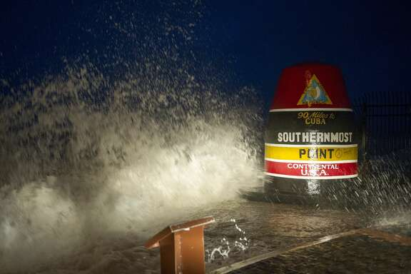 Waves crash against the Southernmost Point in Key West, Fla., Saturday, Sept. 9, 2017. Hurricane Irma's leading edge bent palm trees and spit rain as the storm swirled toward Florida on Saturday. (Rob O'Neal/The Key West Citizen via AP)