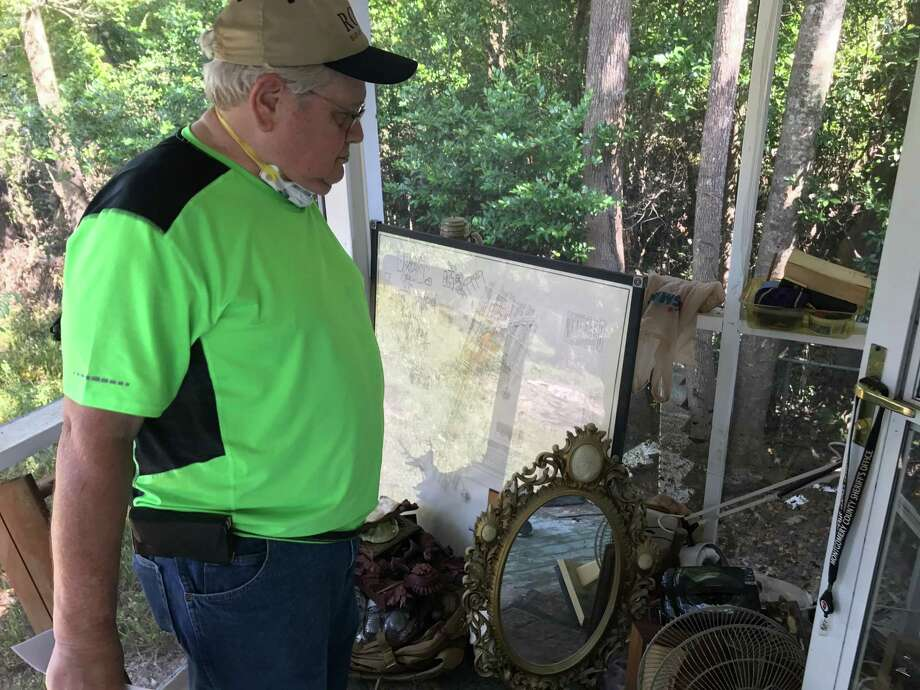 Conroe resident Joseph Newman looks at his late wife's belongings as he works to gut out his two-story home that was flooded by Hurricane Harvey. He's lived in that house for 40 years. Photo: Staff Photo By Meagan Ellsworth