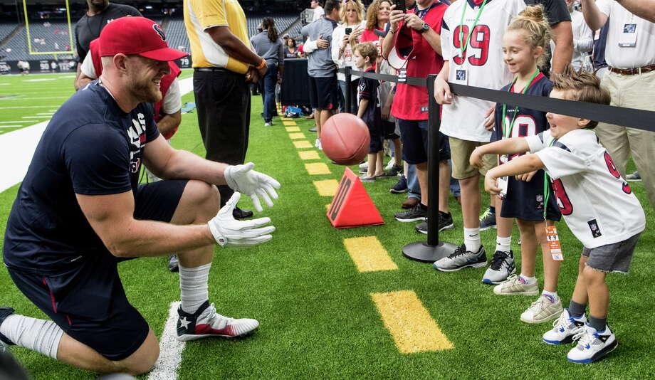 Houston Texans defensive end J.J. Watt tosses a football to a child before the Texans' NFL football game against the Jacksonville Jaguars at NRG Stadium on Sunday, Sept. 10, 2017, in Houston. Photo: Brett Coomer, Houston Chronicle / © 2017 Houston Chronicle
