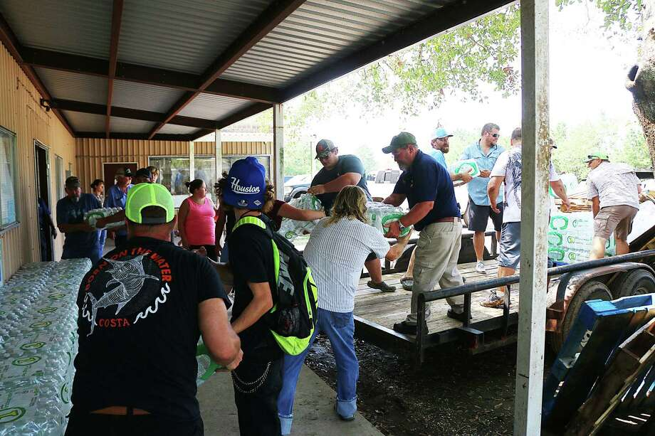 Volunteers, including Constable Robbie Thornton, help unload one of the many trailer loads of supplies brought to the shelter to aid victims from the storm. Photo: David Taylor