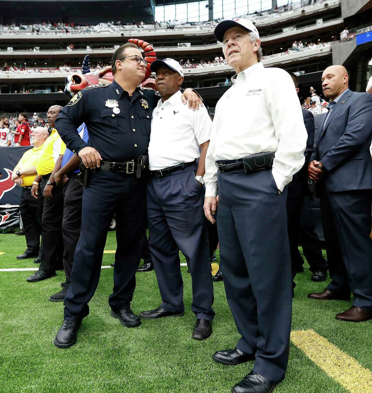 Constable Alan Rosen hugs Mayor Sylvester Turner, standing next to Judge Ed Emmett before the start of an NFL football game at NRG Stadium, Sunday, Sept. 10, 2017, in Houston.