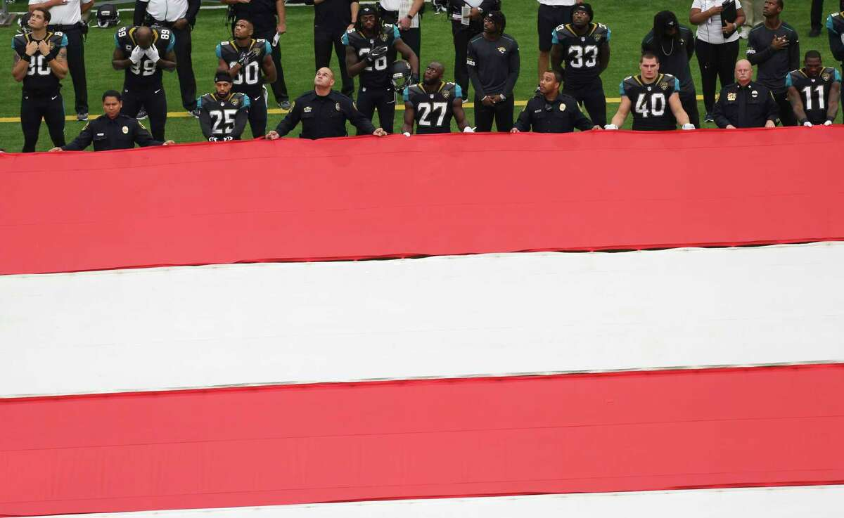 Jacksonville Jaguars players join the first responders to carry the american flag during the opening ceremony of an NFL football game between Houston Texans and Jacksonville Jaguars at NRG Stadium on Sunday, Sept. 10, 2017, in Houston.