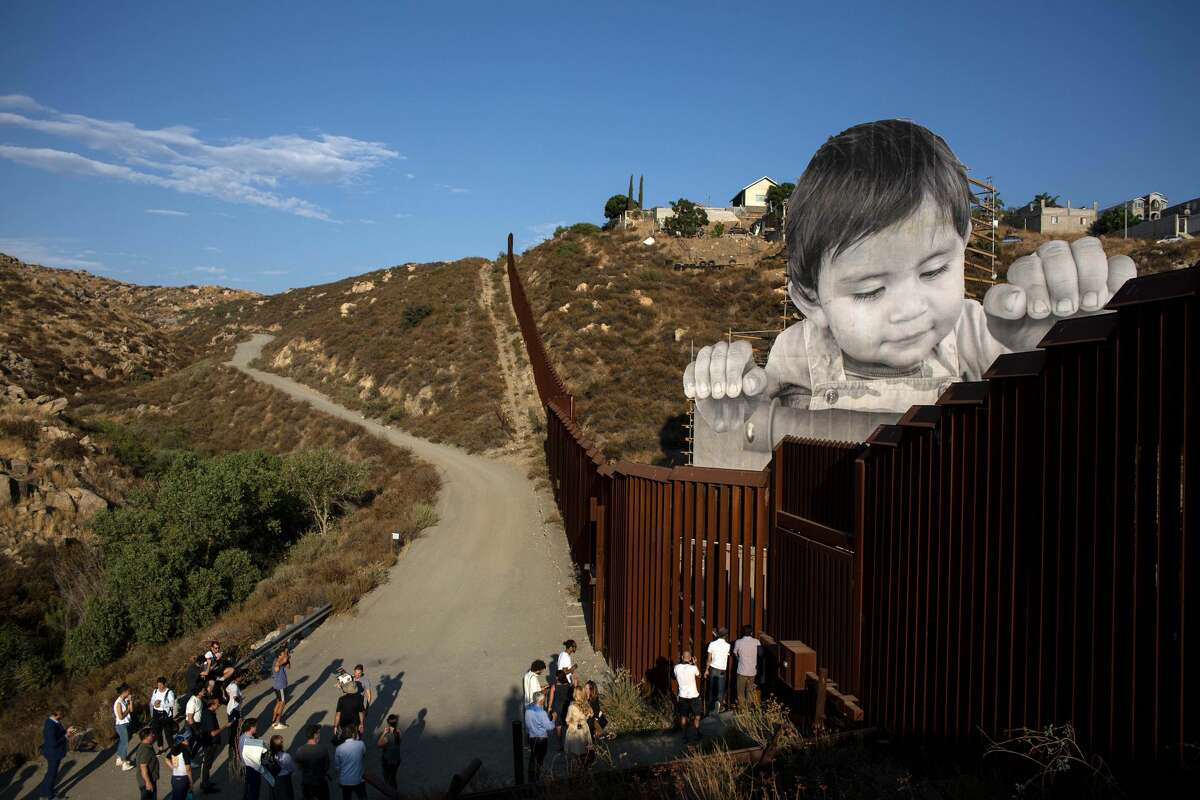 People attend the inauguration of an artwork by French artist JR on the US-Mexico border in Tecate, California, United States on September 6, 2017, / AFP PHOTO / GUILLERMO ARIAS (Photo credit should read GUILLERMO ARIAS/AFP/Getty Images)